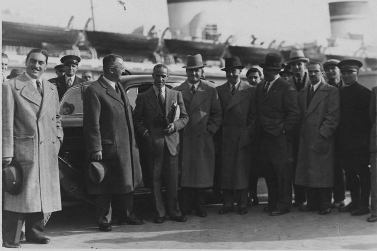Gobbato è il secondo da sinistra, vicino a Tazio Nuvolari dopo la vittoria del pilota mantovano alla Coppa Vanderbilt (New York) del 1936 con la Gran Premio Tipo C, sullo sfondo il transatlantico Rex