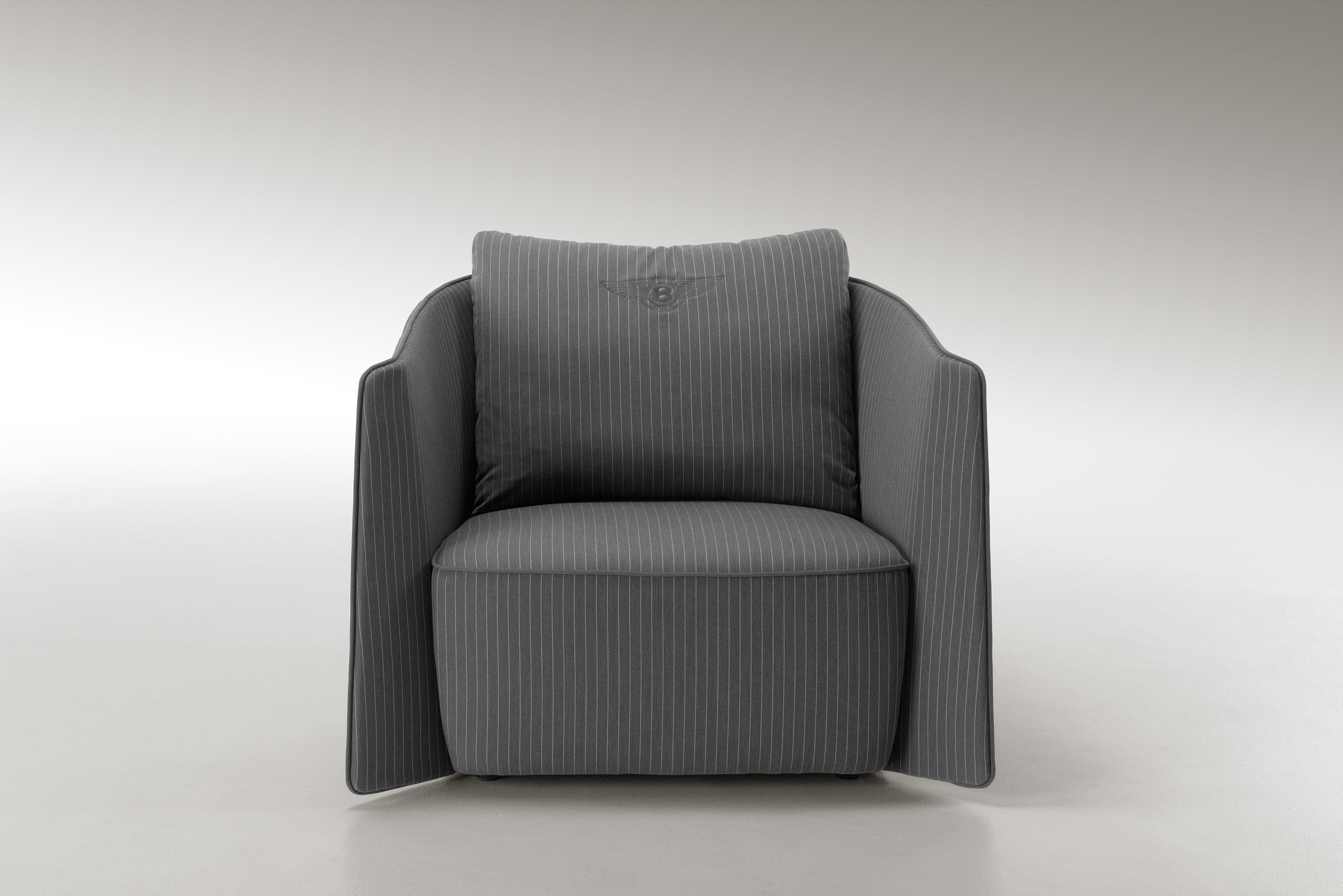 Poltrona Butterfly: realizzata in tesstuto gessato, trapuntato da una raffinata lana grigia.